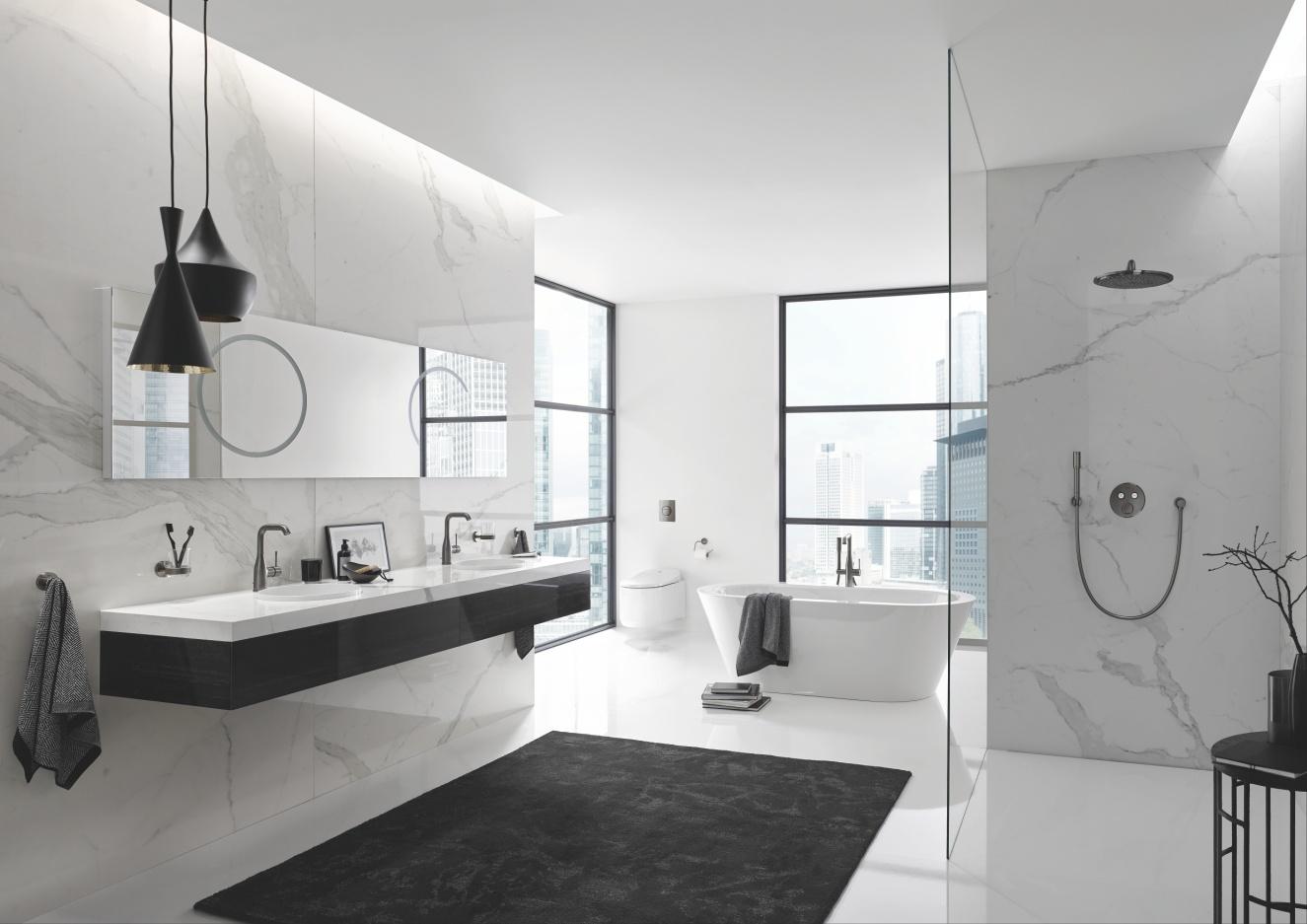 Biała łazienka z 2 umywalkami po lewej i prysznicem z deszczownicą po prawej; z tyłu stoi wanna i duże okno.