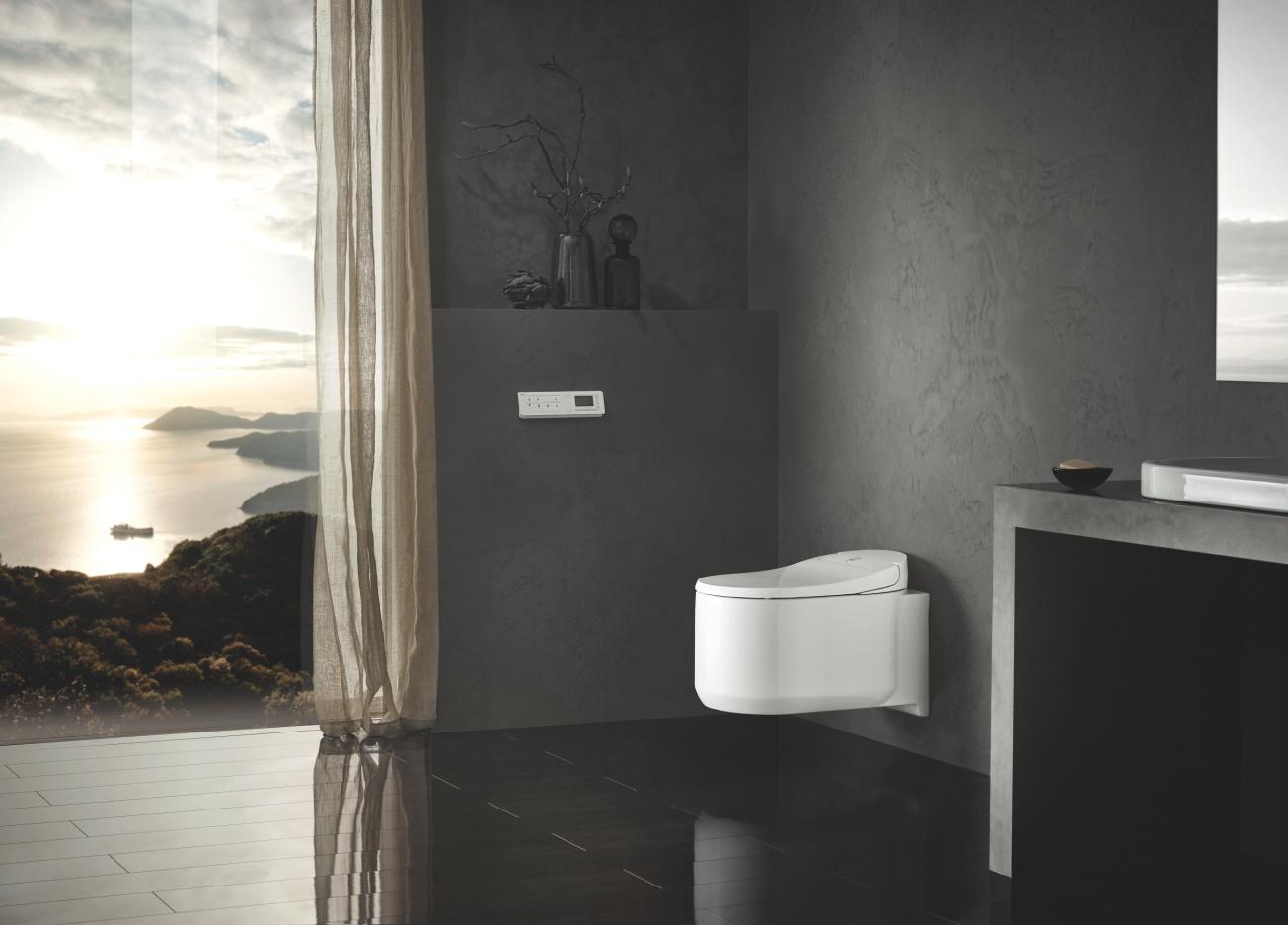Ciemna łazienka z białą toaletą zamontowaną na systemie podtynkowym oraz dużym oknem z widokiem na jezioro